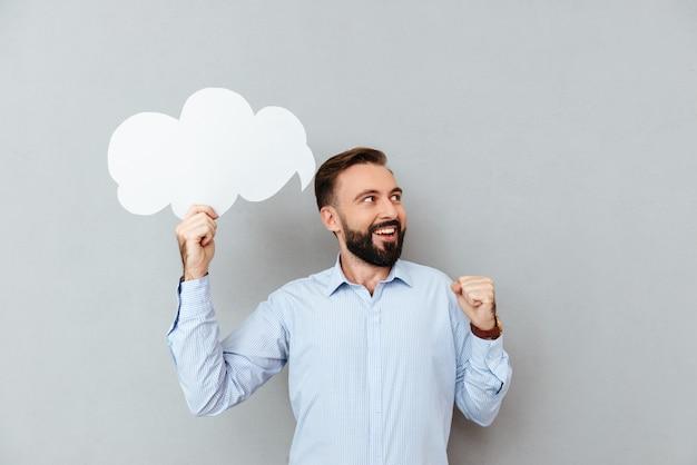 Feliz homem barbudo em roupas de negócios segurando a nuvem do discurso em branco