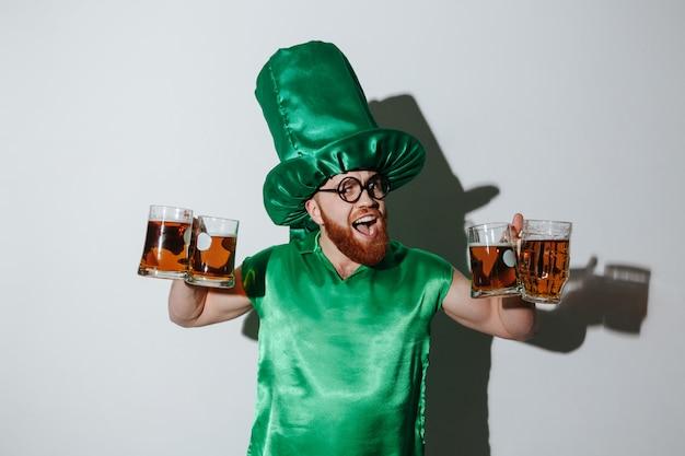 Feliz homem barbudo em traje de st.patriks segurando muitos copos