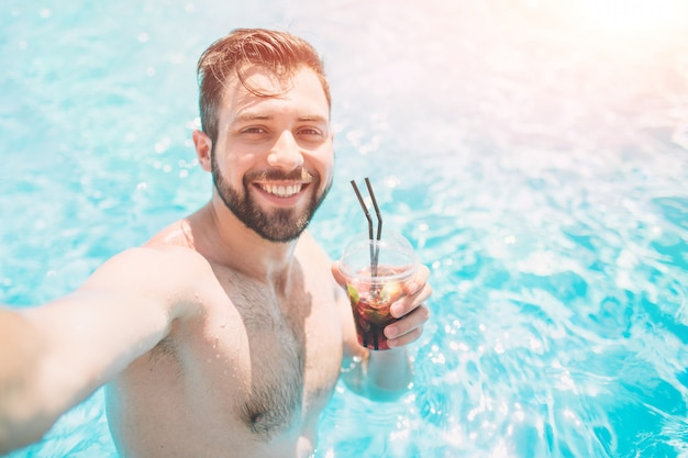 Feliz homem barbudo fazendo selfie na piscina. ele está tomando um coquetel e relaxando.
