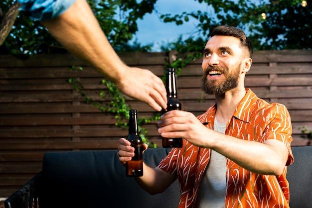 Feliz homem barbudo segurando cervejas