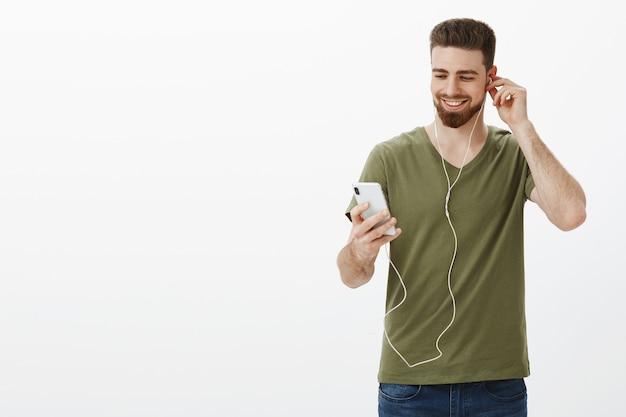 Feliz homem bonito caucasiano com barba na camiseta, colocando o fone de ouvido e parecendo satisfeito com o smartphone, sorrindo, escolhendo música para ouvir na estrada para trabalhar ouvindo música na parede branca