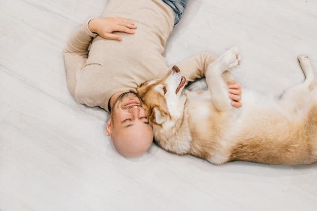 Feliz homem careca com filhote de cachorro husky relaxante no chão.