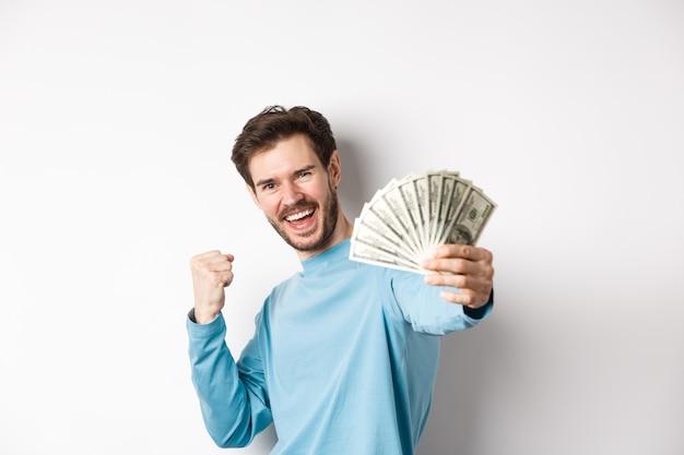 Feliz homem caucasiano estende a mão com dinheiro em dólares, dizendo sim e comemorando a renda, ganhou o prêmio em dinheiro, em pé sobre um fundo branco.