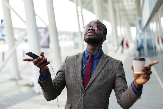Feliz homem de negócios americano africano dança enquanto ouve a música