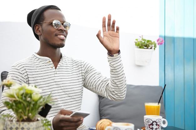 Feliz homem de pele escura, vestindo camiseta listrada de mangas compridas, chapéu e óculos de sol, mensagens on-line usando telefone celular, acenando com a mão enquanto vê um amigo ou chamando o garçom durante o café da manhã no café