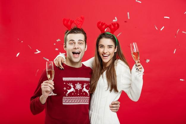 Feliz homem e mulher caucasiano em chapéus de rena comemorando o brinde de natal com flautas de champanhe, felicitando o xmas.