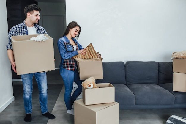 Feliz homem e mulher desembalar coisas de caixas de desenhos animados ao mobiliar o interior