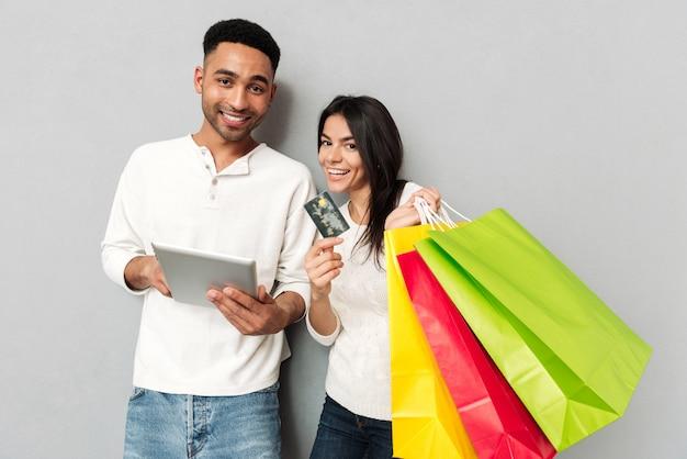 Feliz homem e mulher mostrando tablet e cartão de crédito