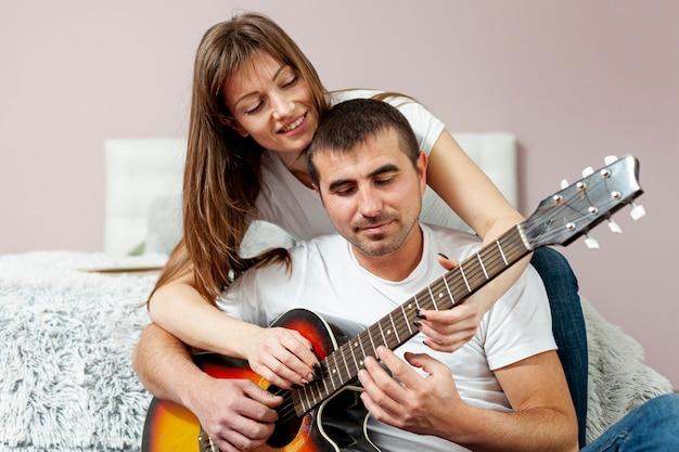 Feliz homem e mulher tocando violão