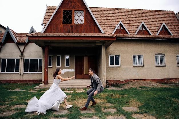 Feliz homem e mulher vestida com roupas oficiais na frente do antigo prédio aconchegante correndo