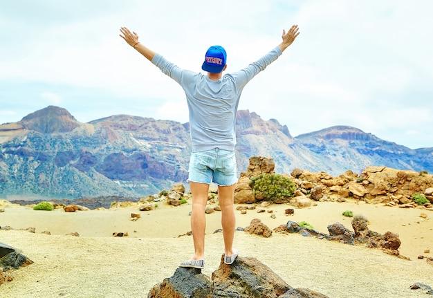 Feliz homem elegante em roupas casuais hipster em pé no penhasco da montanha com as mãos levantadas para o sol e comemorando o sucesso