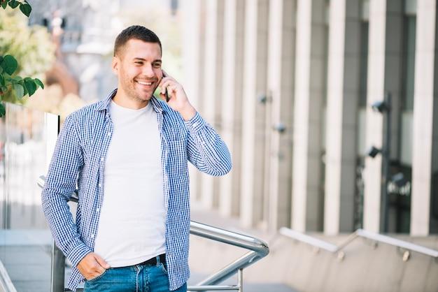 Feliz homem falando no telefone perto do barandrino