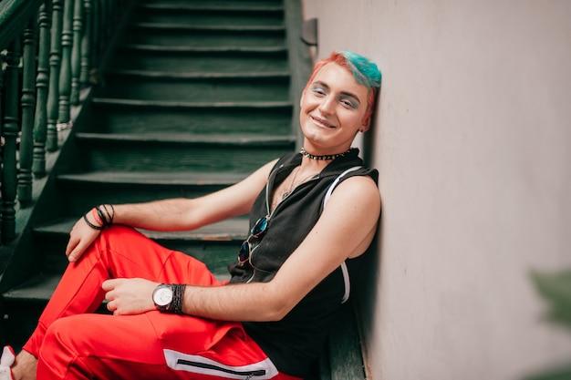 Feliz homem gay com penteado colorido em roupas elegantes, sentado na escada.