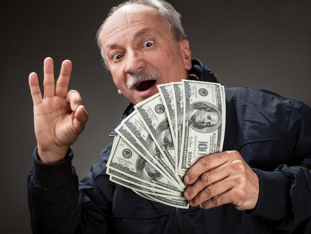 Feliz homem idoso mostrando fã de dinheiro