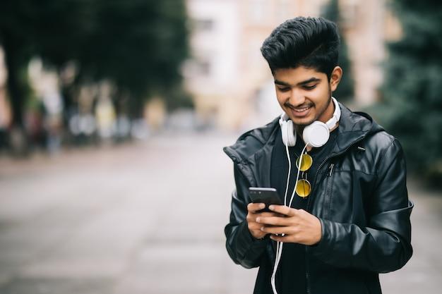 Feliz homem indiano andando e usando um telefone inteligente para ouvir música com fones de ouvido