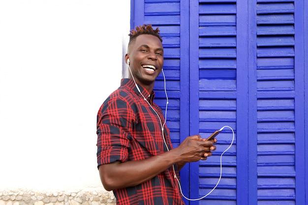 Feliz, homem jovem, ficar, ao ar livre, escutar música, com, telefone móvel