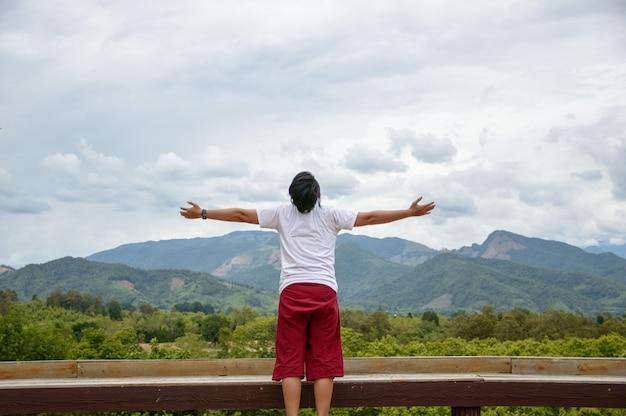 Feliz, homem jovem, ficar, com, braços levantados, em, chuvoso, estação, montanhas