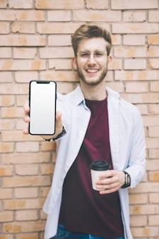 Feliz, homem jovem, mostrando, telefone móvel, com, em branco, tela branca