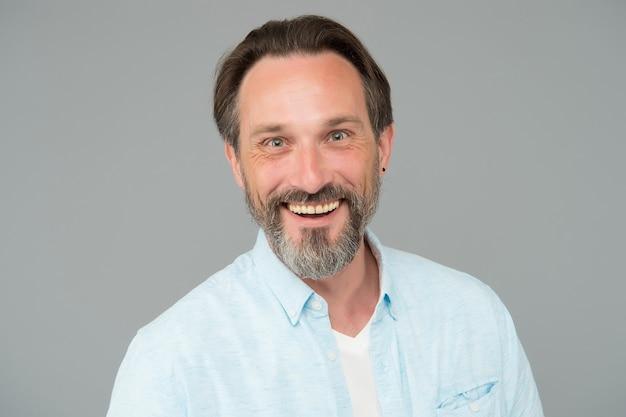 Feliz homem maduro com dentes saudáveis e rosto barbudo com barba por fazer sorrir fundo cinza, dental.