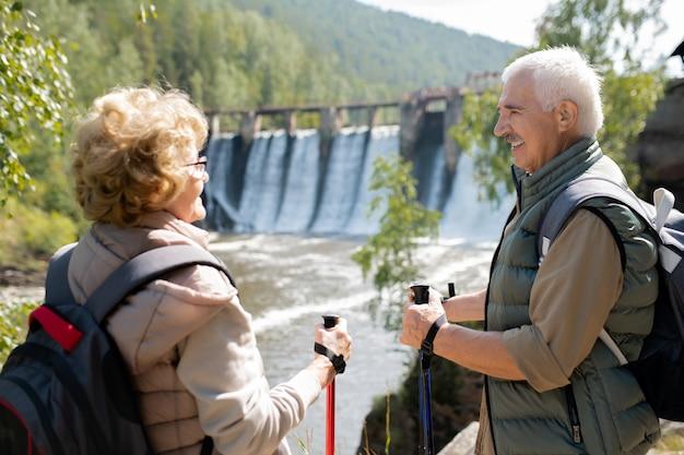 Feliz homem maduro e mulher em trajes esportivos conversando em um ambiente natural enquanto desfruta de sua viagem de caminhada
