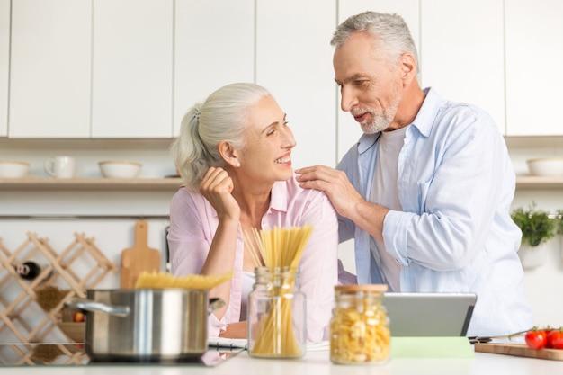 Feliz homem maduro em pé perto de mulher madura alegre usando tablet