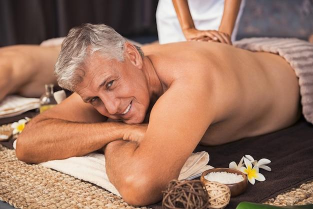 Feliz homem maduro, recebendo tratamento de spa