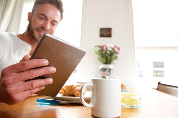 Feliz homem mais velho com saudável café da manhã segurando o tablet