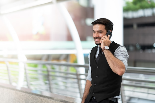 Feliz, homem negócios fica, ao ar livre, chamando, telefone móvel, cidade
