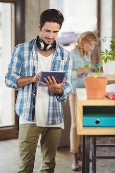 Feliz, homem negócios, segurando, tablete digital, em, criativo, escritório