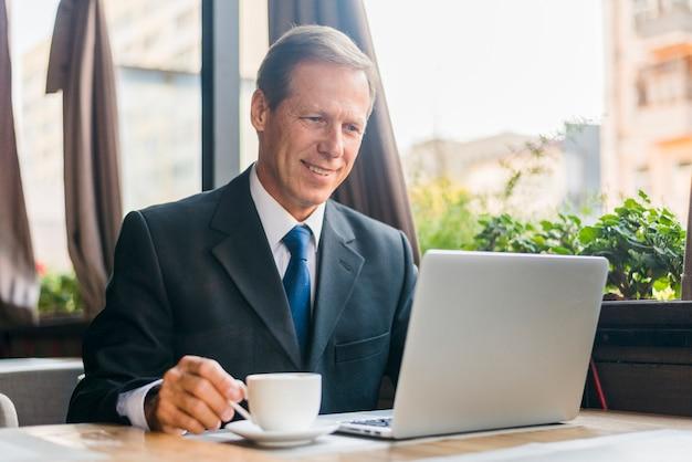 Feliz, homem negócios, usando computador portátil, com, xícara café, ligado, escrivaninha madeira