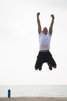 Feliz homem poderoso com braços levantados pulando