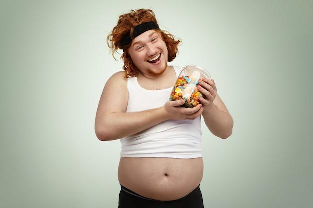 Feliz homem ruivo bonito vestindo faixa de cabelo e camiseta encolhida, segurando o pote de vidro de doces, regozijando-se com o delicioso mas não saudável pé lixo após treinamento cardio, combatendo o excesso de peso