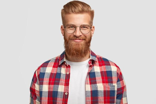 Feliz homem ruivo com expressão satisfeita, usa óculos e camisa quadriculada da moda, regozija-se com o projeto feito com sucesso, posa sozinho contra uma parede branca. pessoas, emoções, estilo de vida