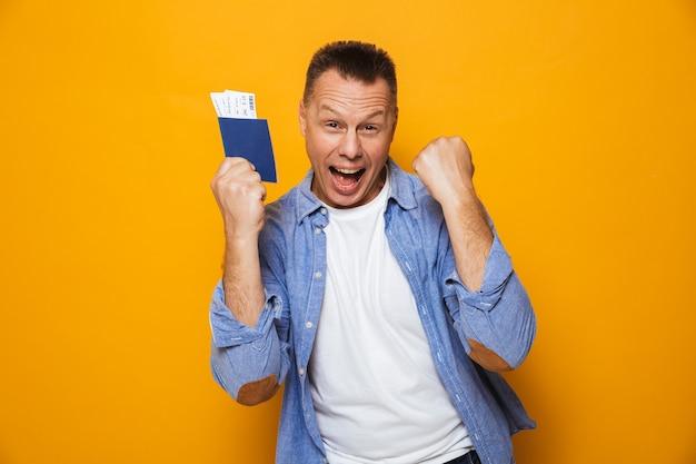 Feliz homem segurando o passaporte fazer gesto de vencedor.