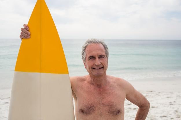 Feliz homem sênior em pé na praia com uma prancha de surf