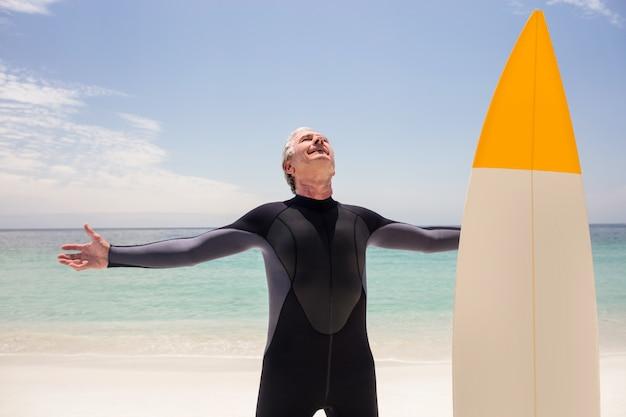 Feliz homem sênior em roupa de mergulho em pé com os braços estendidos