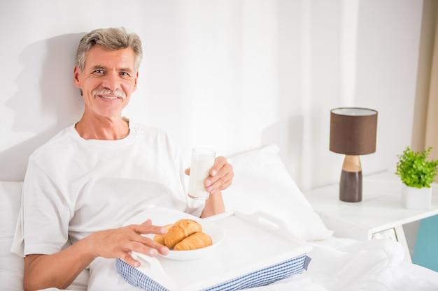 Feliz homem sênior está tomando café da manhã na cama.