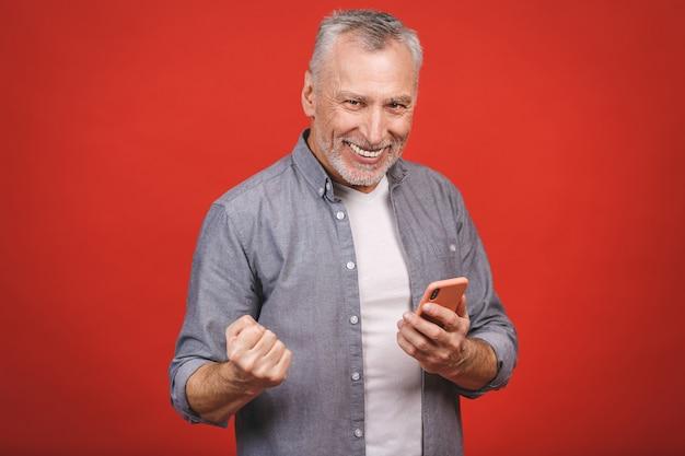 Feliz homem sênior maduro em casual usando smartphone e fazendo gesto vencedor isolado sobre parede vermelha. usando o telefone