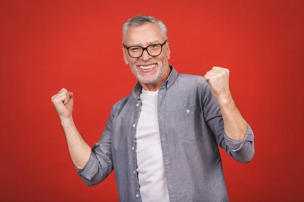 Feliz homem sênior maduro em casual usando smartphone e fazendo gesto vencedor isolado sobre parede vermelha.