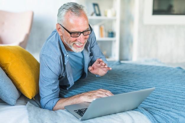 Feliz, homem sênior, mentindo cama, usando computador portátil, casa