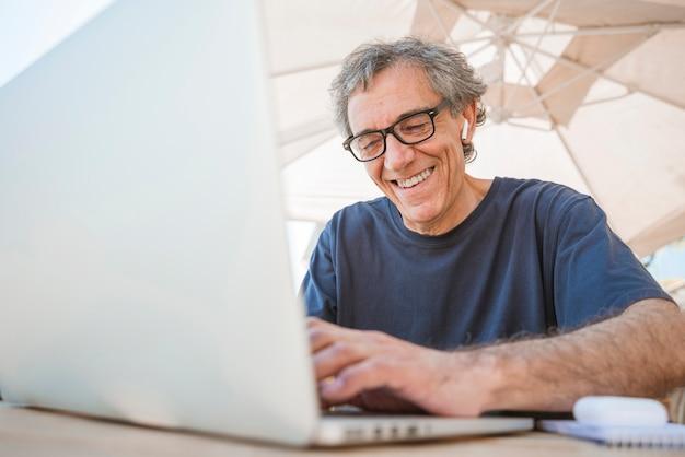 Feliz homem sênior usando óculos usando o laptop no café ao ar livre