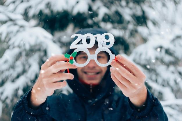 Feliz, homem sorridente, segurando, partido, ano novo, óculos, com, números, 2019, em, inverno, parque