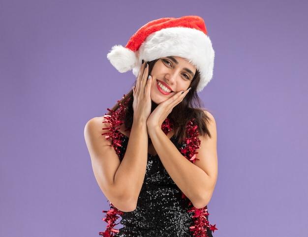Feliz inclinando a cabeça jovem linda com chapéu de natal com guirlanda no pescoço e bochechas cobertas com as mãos isoladas no fundo roxo