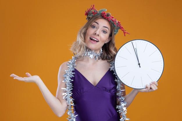 Feliz inclinando a cabeça jovem linda com vestido roxo e grinalda com guirlanda no pescoço segurando um relógio de parede isolado no fundo marrom