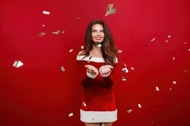 Feliz inspirada jovem comemorando o ano novo com sorriso, foto de estúdio de brunettelaughing feminino mo ...