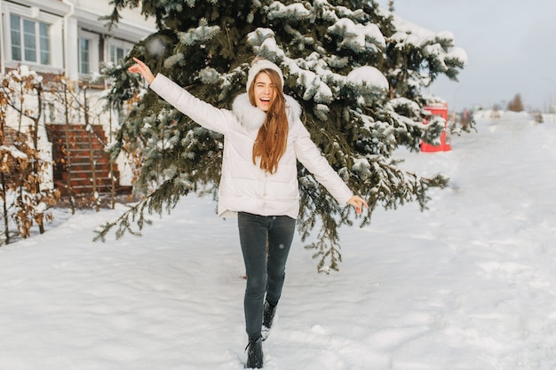 Feliz inverno congelado na manhã ensolarada na rua de uma mulher bonita alegre se divertindo na neve.