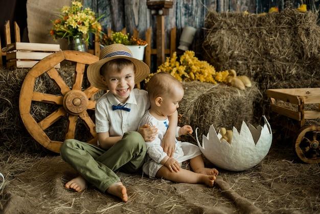 Feliz irmão e irmã caucasianos com roupas de linho, sentam-se na superfície do feno na zona de páscoa. feriado de páscoa para crianças