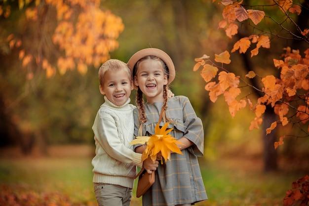 Feliz irmão e irmã em uma caminhada no parque outono