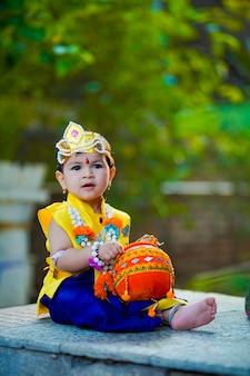 Feliz janmashtami cartão mostrando garotinho indiano posando como shri krishna ou kanha / kanhaiya com imagem dahi handi e flores coloridas.