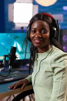 Feliz jogador africano esport durante o campeonato ao vivo em uma sala com luz de néon. streaming de videogames virais para se divertir usando fones de ouvido e teclado para campeonatos online.
